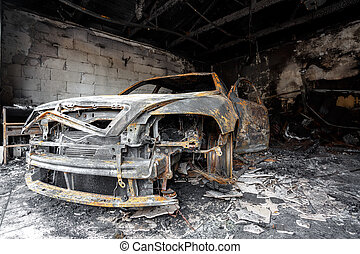 Close up photo of a burned out car in garage after fire for...