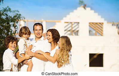 Family building a new house - Happy and big family builds a...