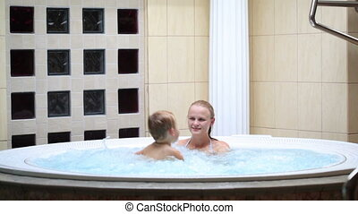 Mother enjoying a spa bath with her son