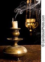 Blown out candle in antique candle stick and in the...