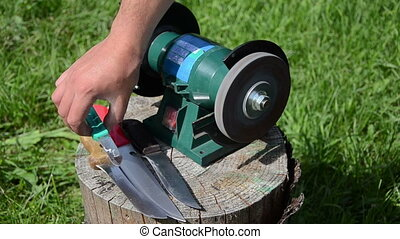 blade sharpen hand - man hand turns on electric sharpener...