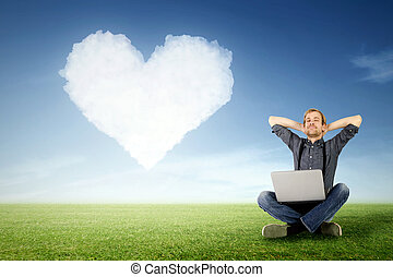 message of love - a man sits relaxed with laptop on the...