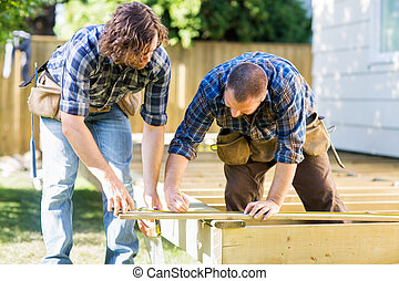 Building a Deck - Mid adult carpenter marking wood while...