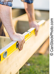 Carpenters Hands Checking Level Of Wood - Closeup of...