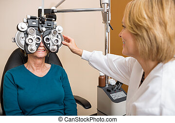Optician Examining Patient's Vision - Female optician...