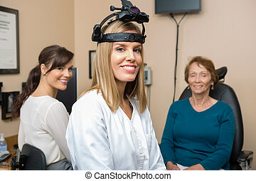 Optometrists With Senior Patient In Store - Portrait of...