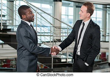 Business People - African businessman shaking hands with a...