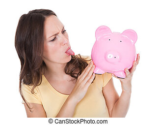 Woman Making Face Looking At Piggybank - Close-up Of A Young...