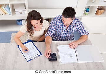 Couple Calculating Bills - Portrait Of A Young Couple...