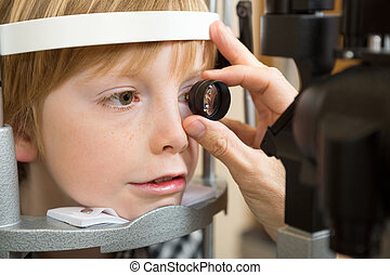 Opticians Hand Examining Boys Retina - Closeup of male...