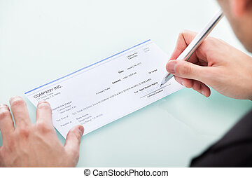 Businessman Signing On Cheque - Young Businessman Filling...