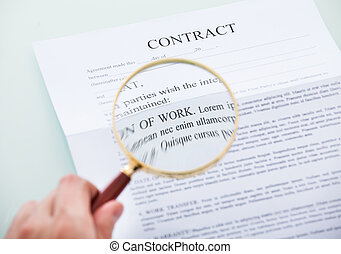 Hand Holding Magnifying Glass Over Contract - Close-up Of...