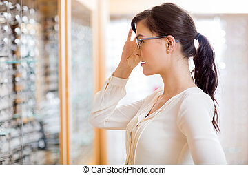 Woman Trying New Glasses At Optician Store - Side view of...