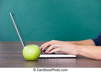 Person Using Laptop Besides Green Apple - Close-up Of...