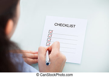 Businesswoman Marking On Checklist - High Angle View Of A...
