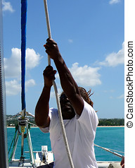 Pulling the sail rigging tight - A crewman pulls the...