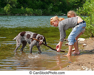 Girls and Dog 3 - Two young girls play with dog at river....