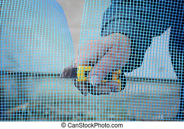 Home renovation - Close up of worker hands cut mesh for...