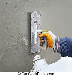 Home renovation - Worker spreading mortar over styrofoam...