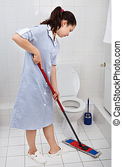 Young Maid Cleaning Toilet - Portrait Of Young Maid In...