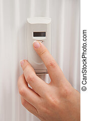Person's Hand Using Digital Thermostat - Close-up Of...