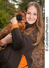 Cuddling with the dog - Young teenage girl is having a nice...