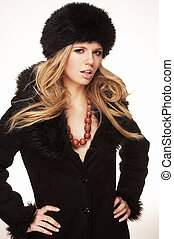 Woman in black fur hat and coat - on white background