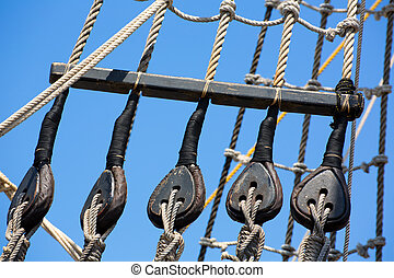 Vintage wooden boat pulley and ropes detail under blue sky