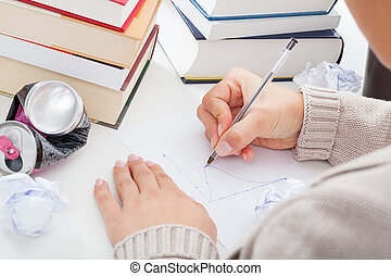 Student drawing a chart - Student solving an equation and...