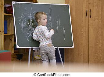 Creative little boy drawing on a chalkboard