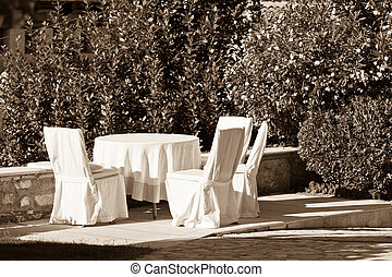 Outdoor empty summer cafe table with chairs Sepia