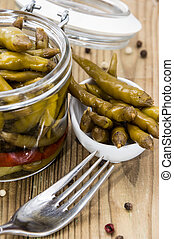 Pickled Chilis in a glass on wooden background