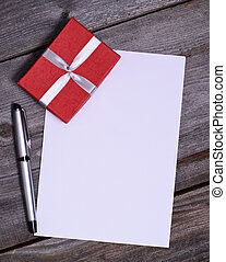 Blank paper with gift on wooden background