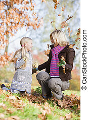 Woman and young girl outdoors in park playing in leaves and...