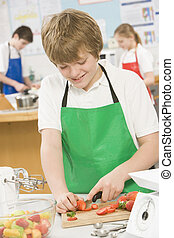 Male student slicing berries in cooking class