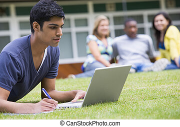 Student outdoors on lawn using laptop with other students in...