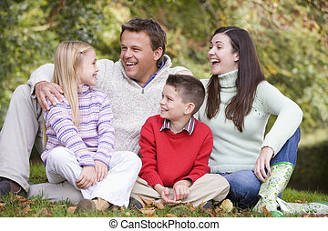 Family sitting outdoors laughing (selective focus)