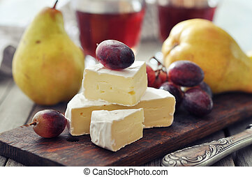 Camembert cheese and fresh fruits on wooden background