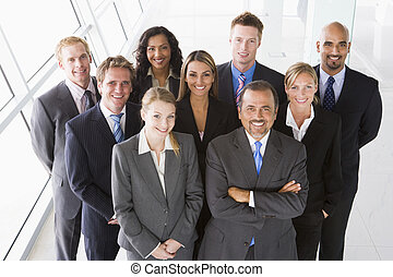 Group of co-workers standing in office space smiling (high key)