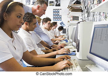 Students working on computer workstations with teacher