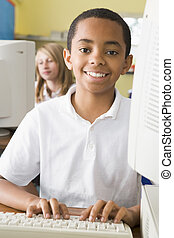 Student at computer terminal typing with student in...
