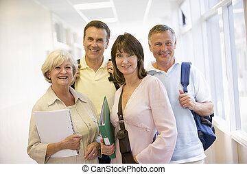 Four people standing in corridor with books (high key)