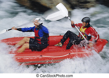 Two kayakers rowing in rapids and smiling selective focus