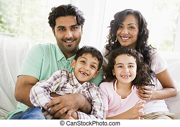 Family in living room sitting on sofa smiling (high key)