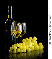 Bottle of wine and a bunch of white grapes - A bottle and a...