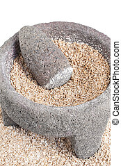 Grinding wheat - Closeup of stone mortar and pestle filled...