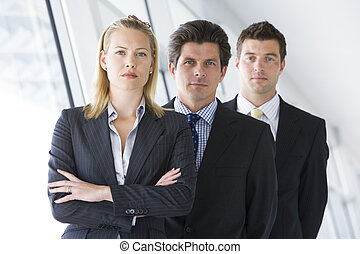 Three businesspeople standing in corridor