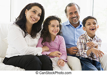 Grandparents sitting in living room with grandchildren smiling (high key)
