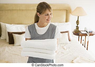 empregada, segurando, Toalhas, hotel, sala, sorrindo
