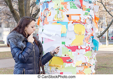 Woman reading a notice off a noticeboard - Woman reading a...